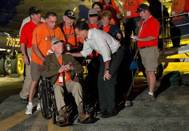 FILE - In this Sept. 26, 2012, file photo Republican presidential candidate, former Massachusetts Gov. Mitt Romney shakes hands with World War II and Korean War veterans returning on an Honor Flight f