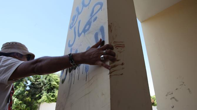 "A Libyan man explains that the bloodstains on the column are from one the American staff members who grabbed the edge of the column while he was evacuated, after an attack that killed four Americans, including Ambassador Chris Stevens on the night of Tuesday, Sept. 11, 2012, in Benghazi, Libya, Thursday, Sept. 13, 2012.  The American ambassador to Libya and three other Americans were killed when a mob of protesters and gunmen overwhelmed the U.S. Consulate in Benghazi, setting fire to it in outrage over a film that ridicules Islam's Prophet Muhammad. Ambassador Chris Stevens, 52, died as he and a group of embassy employees went to the consulate to try to evacuate staff as a crowd of hundreds attacked the consulate Tuesday evening, many of them firing machine-guns and rocket-propelled grenades. Arabic writing reads, "" Villa of Jamal al Beshary"". which was written by the owner to protect the property from another attack. (AP Photo/Mohammad Hannon)"