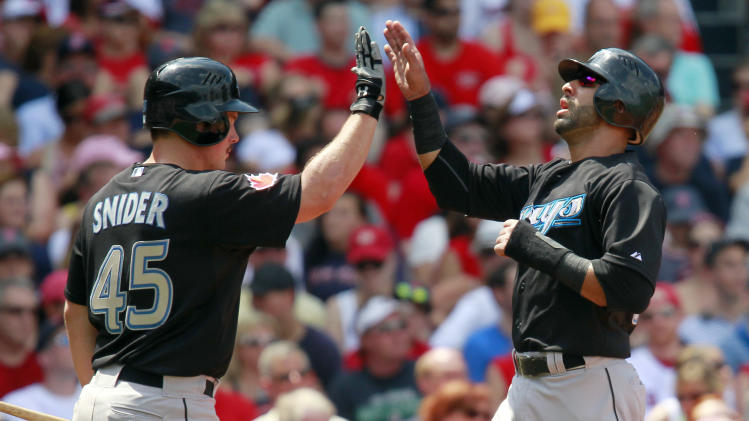 Toronto Blue Jays' Jose Bautista, right, celebrates with teammate Travis Snider (45) after scoring on an RBI single by Aaron Hill in the third inning of a baseball game against the Boston Red Sox in Boston, Monday, July 4, 2011. (AP Photo/Michael Dwyer)