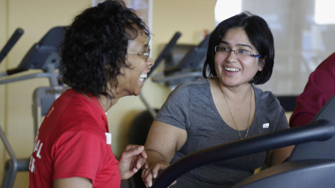 In this March 26, 2013 photo, Aidee Diaz, 36, right, exercises with personal trainer Angela Appleton at the Rauner Family YMCA on Chicago's South Side. Diaz has lost 100 pounds since a simultaneous robotic kidney transplant and obesity surgery in July 2012 at the University of Illinois Hospital & Health Sciences System in Chicago. Diaz says the YMCA workouts are helping her get in shape. (AP Photo/M. Spencer Green)