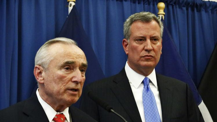 Bratton speaks to the media next to Blasio during a news conference in Brooklyn