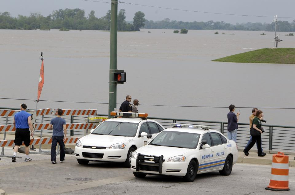 Police block access to Riverside Drive as pedestrians walk around and floodwater is seen in the background Saturday, May 7, 2011, in Memphis, Tenn. Communities all along the banks of the Mississippi are keeping a close eye on the river's rise with the crest in Memphis not expected until Wednesday. (AP Photo/Jeff Roberson)