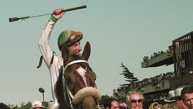 FILE - In this June 8, 1996 file photo,jockey Rene Douglas waves to the crowd after his victory aboard Editor's Note in the Belmont Stakes in Elmont, New York. It had been nearly four years since the Panamanian jockey was paralyzed when his horse fell on top of him at Arlington Park and this week was the first time he had been to a track. (AP Photo/Bebeto Matthews, File)