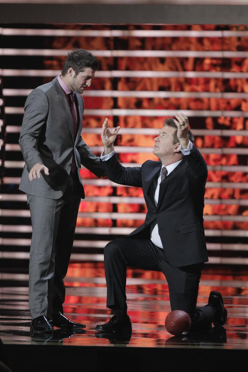 Denver Broncos' Tim Tebow corrects Alec Baldwin on his Tebowing form during the inaugural NFL Honors show Saturday, Feb. 4, 2012, in Indianapolis.The New York Giants will face the New England Patriots in the NFL football's Super Bowl XLVI in Indianapolis on Feb. 5. (AP Photo/Charlie Riedel)