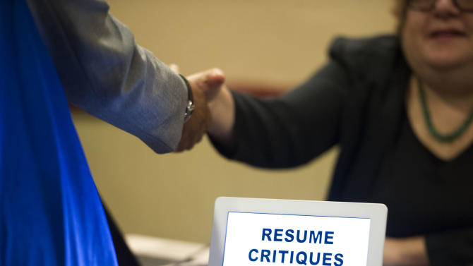 In this Thursday, May 30, 3013 photo, a job seeker stops at a table offering resume critiques during a job fair held in Atlanta. The Labor Department reports on the number of Americans who applied for unemployment benefits for the first time last week Thursday June 20, 2013. (AP Photo/John Amis)