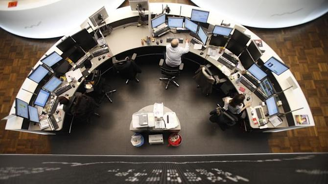 Traders work at their desks below the DAX board at the Frankfurt stock exchange