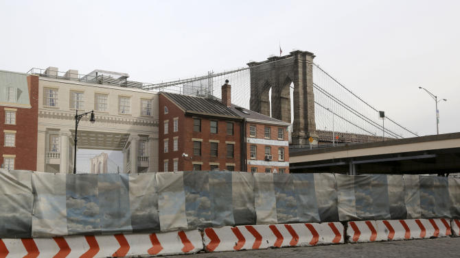 In this Thursday, Feb. 7, 2013 photo, construction materials are stored behind a cloud painted fence on Peck Slip in New York. Nearly four months after Superstorm Sandy hit, the historic cobblestone streets near the water's edge in lower Manhattan are eerily deserted, and among local business owners, there is a pervasive sense that their plight has been ignored by the rest of Manhattan. (AP Photo/Mary Altaffer)
