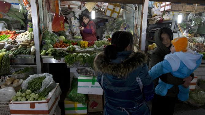 A woman with a child stands near vegetable stalls in Beijing Friday, Jan. 11, 2013. China's inflation spiked to a six-month high in December after a freezing winter pushed up vegetable prices, possibly complicating efforts to sustain a shaky economic recovery, the National Bureau of Statistics reported Friday. (AP Photo/Ng Han Guan)