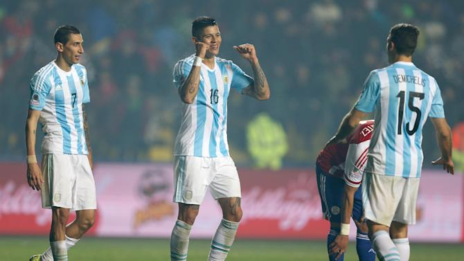 Argentina's Marcos Rojo, center, celebrates with Martin Demichelis and Angel Di Maria, left, at the end of a Copa America semifinal soccer match against Paraguay at the Ester Roa Rebolledo Stadium in Concepcion, Chile, Tuesday, June 30, 2015. Argentina won 6-1.(AP Photo/Andre Penner)