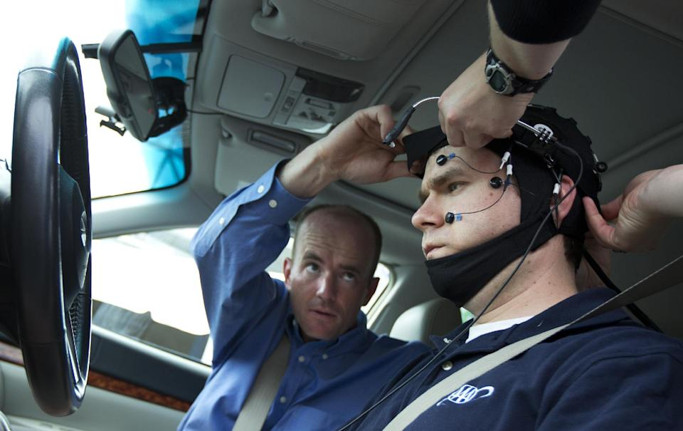 Russ Martin of triple A, is assisted by Joel Cooper, left, hooking the electroencephalographic (EEG)-configured skull cap to the research vehicle during a demonstrations in support of their new study on distracted driving in Landover, Md., Tuesday, June 11, 2013.   (AP Photo/Manuel Balce Ceneta)