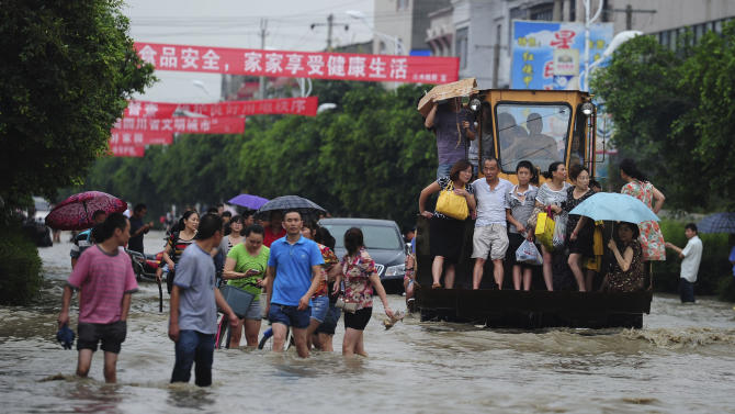 Residents are evacuated through a flooded street by an excavator in Guanghan city in southwestern China's Sichuan province Tuesday July 9, 2013. (AP Photo) CHINA OUT