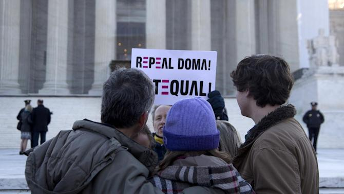 "A woman holds up a sign that reads ""REPEAL DOMA,"" the Defense of Marriage Act, as a group from Alabama prays in front of the Supreme Court in Washington, Wednesday, March 27, 2013. In the second of back-to-back gay marriage case, the Supreme Court is turning to a constitutional challenge to the law that prevents legally married gay Americans from collecting federal benefits generally available to straight married couples. (AP Photo/Carolyn Kaster)"