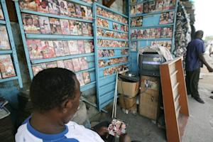 A man selling CDs and DVDs of Nigerian Nollywood (combination …