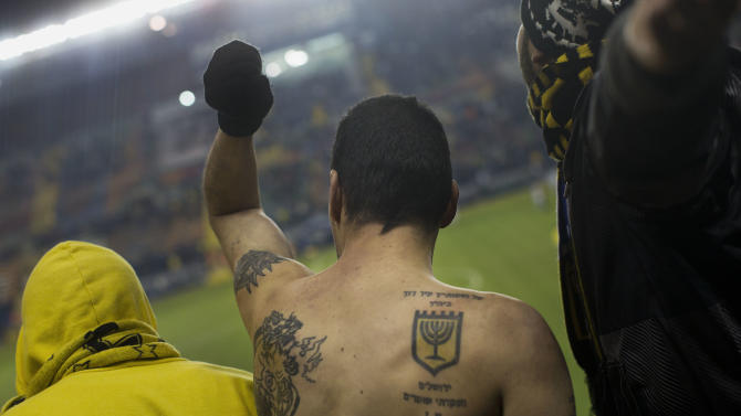 "In this Tuesday, Jan. 29, 2013 photo, Beitar Jerusalem F.C. soccer supporters watch a State Cup soccer match against Maccabi Umm al-Fahm F.C. at the Teddy Stadium in Jerusalem. Beitar has long tried to quell a tight-knit group of fans that calls itself ""La Familia"" and whose behavior has had the team docked points and forced it to play before empty stadiums. The group is routinely abusive toward opposing players, taunting them with racist and anti-Arab chants. The right tattoo shows the Beitar Jerusalem logo and reads ""I have set watchmen on your walls, Jerusalem; they shall never hold their peace day nor night."" (AP Photo/Bernat Armangue)"
