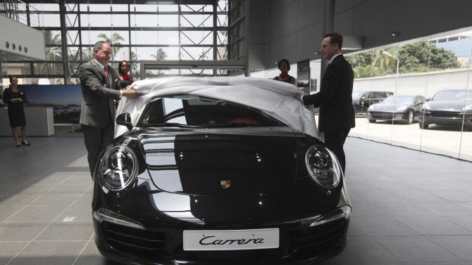 Staff uncover a new Porsche Carrera 911 at a showroom for the luxury brand on Victoria Island in Lagos, Nigeria, Friday March 16, 2012. The wealthy elite in Nigeria _ upstart business owners, oil industry executives and corrupt politicians _ have a healthy appetite for top shelf brands, but have had to shop in Dubai, London and Paris to find such brands. Now though, sellers of luxury goods are opening stores in Nigeria where seemingly gratuitous displays of wealth are the norm. (AP Photos/Sunday Alamba)