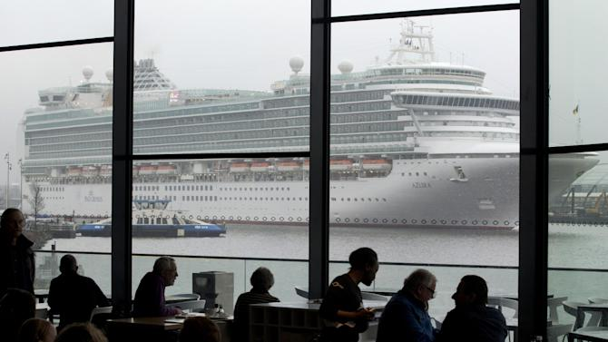 FILE - In this Jan. 9, 2013 file photo the Italian-built cruise ship MS Azura sails past the EYE film institute as it leaves the port of Amsterdam, Netherlands. One of Amsterdam's newest landmarks is a stark, white film institute, called the EYE, perched on northern bank of the IJ waterway. While you have to pay to take in a movie, the cafe and its terrace are open to all who are prepared to buy a cup of coffee or light meal and offer a front-row seat to watch barges chug along the IJ against a backdrop of the city skyline. (AP Photo/Peter Dejong)