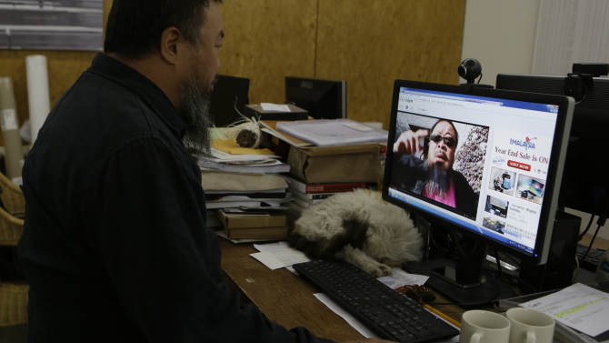 Chinese dissident artist Ai Weiwei plays a video clip he uploaded on Youtube on a computer in Beijing, China, Thursday, Oct. 25, 2012. In the video, Ai sports a neon-pink T-shirt, black jacket and dark sunglasses and energetically mimics rodeo-style dance moves made famous by South Korean rapper PSY whose original video became an Internet sensation. (AP Photo/Ng Han Guan)