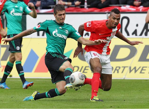 Mainz's Maxim Choupo-Moting of Cameroon, right, and Schalke's Roman Neustaedter challenge for the ball during a German soccer Bundesliga match between FSV Mainz 05 and FC Schalke 04 in Mainz, Germany,