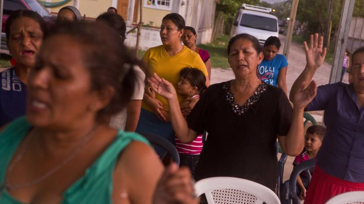In this photo taken Saturday, July 19, 2014, Elsa Ramirez, 27, in yellow, deported from the United States with her children a day earlier, prays at a local outdoor church youth meeting, in Tocoa, Honduras. After her husband's death, Ramirez decided to head north. In less than a month's time and many thousands of miles later, a U.S. Immigration and Customs Enforcement flight brought Ramirez back to where she started. Ramirez does not know what the future will bring. She could hide out in her mother's home for a time, she said, perhaps work as a cook. (AP Photo/Esteban Felix)