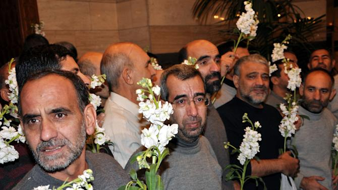 In this photo released by the Syrian official news agency SANA, freed Iranian hostages who were captured by the Syrian rebels since August, hold roses as they gather at a hotel, in Damascus, Syria, Wednesday Jan. 9, 2013. Rebels freed 48 Iranians on Wednesday in exchange for more than 2,000 prisoners, including women and children, held by Syrian authorities — a deal struck after rare negotiations involving regional powers Turkey, Qatar and Iran. (AP Photo/SANA)
