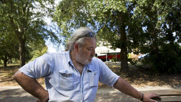 Richard Smith, who was laid off from a factory owned by BWAY Corporation in 2010, rests after moving wooden pallets in his front yard in Toccoa