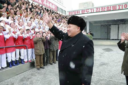 North Korean leader Kim Jong Un waves to workers during a visit to the Pyongyang Children's Foodstuff Factory