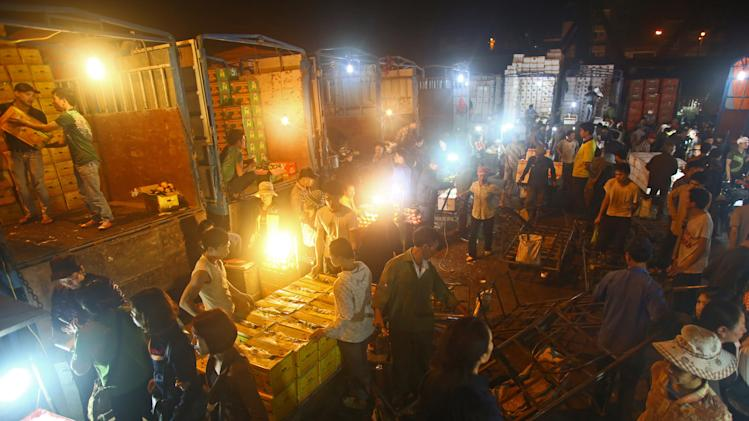 In this March 9, 2013 photo,  porters unload boxes of Chinese fruits near traders at Long Bien wholesale market for fruits and vegetables in Hanoi, Vietnam. While fears about the safety of Chinese food products are often well founded, in Vietnam they are so tangled up with anti-Chinese sentiment it is hard to tell where one begins and the other ends. More than 1,000 years of occupation, a bloody border war in 1979 and renewed assertiveness by China in pushing territorial claims in the South China Sea mean that tales of Chinese perfidy find fertile soil in which to grow.(AP Photo/Na Son Nguyen)