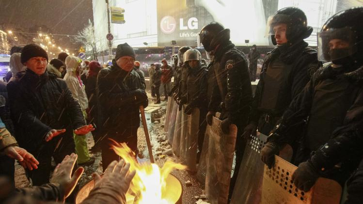 Protestors warm themselves near a fire burning in a steel drum as Interior Ministry personnel block a street during a gathering of supporters of EU integration in Kiev