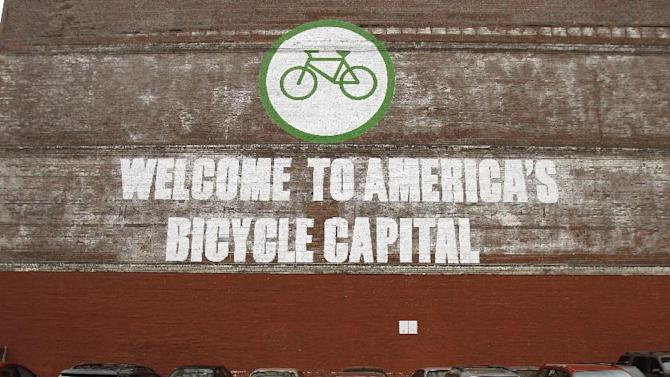 A wall painting trumpets the fact that the city is very bike-friendly in downtown Portland, Ore., Wednesday, Sept. 19, 2012. Researchers at Portland State University found that the Portland atmosphere and culture is a magnet for the young and college educated, even though a disproportionate share of them are working in part-time jobs or positions that don't require a college degree. (AP Photo/Don Ryan)