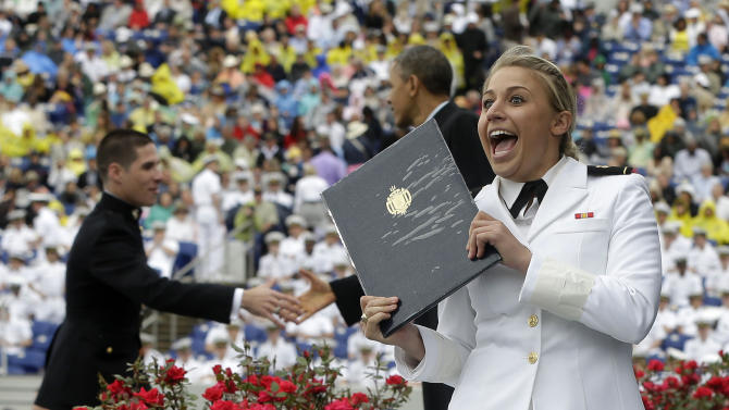 President Barack Obama congratulates a graduate as another one celebrates at the United States Naval Academy commencement ceremony in Annapolis, Md., Friday, May 24, 2013. (AP Photo/Pablo Martinez Monsivais)