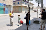 A Syrian family walks past closed shops as they flee the Shaar neighborhood of the restive city of Aleppo. Syrian rebels staved off a fightback by regime forces in Aleppo on Saturday amid growing concern about the risks of reprisals against civilians in the country&#39;s commercial capital