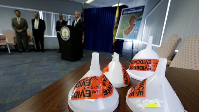 """Funnels confiscated during an investigation dubbed """"Operation Swill,"""" in which 29 bars and restaurants in New Jersey are accused of putting cheap booze in premium brand liquor bottles and selling it, are displayed during a news conference, Thursday, May 23, 2013, in Trenton, N.J. Thirteen of the restaurants cited are TGI Fridays located in central and northern New Jersey. (AP Photo/Julio Cortez)"""