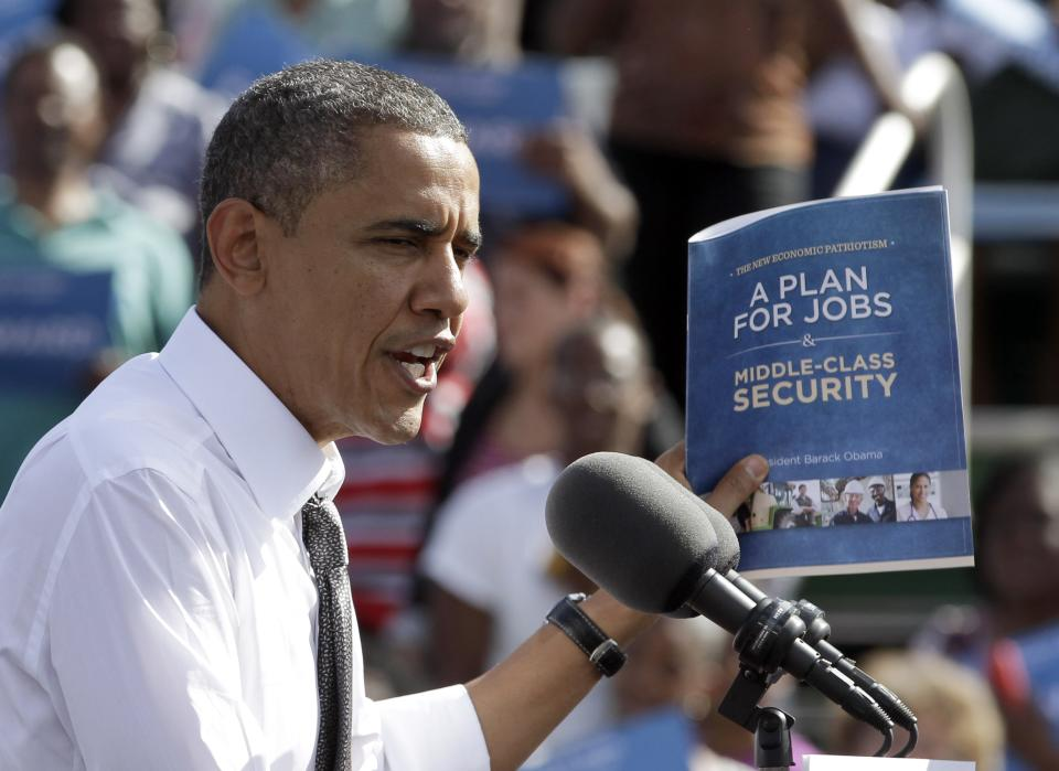 President Barack Obama holds up a copy of his plan for jobs as he speaks to supporters during a campaign stop in Delray Beach, Fla., Tuesday, Oct. 23, 2012, a day after his last debate with Republican presidential candidate, former Massachusetts Gov. Mitt Romney. (AP Photo/Alan Diaz)