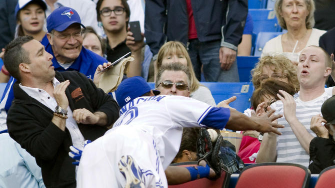 Toronto Blue Jays' Edwin Encarnacion dives into the stands to make the catch to out Tampa Bay Rays' B.J. Upton during the first inning of a baseball game, Tuesday, May 15, 2012, in Toronto. (AP Photo/The Canadian Press, Chris Young)