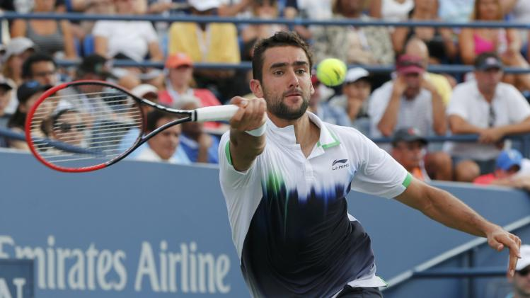 Cilic of Croatia hits a return to Simon of France during their fourth round match at the 2014 U.S. Open tennis tournament in New York