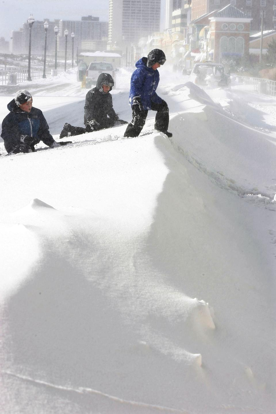 Children play on a mound of snow on The Boardwalk, Monday, Dec. 27, 2010, in Atlantic City, N.J. (AP Photo/Mel Evans)