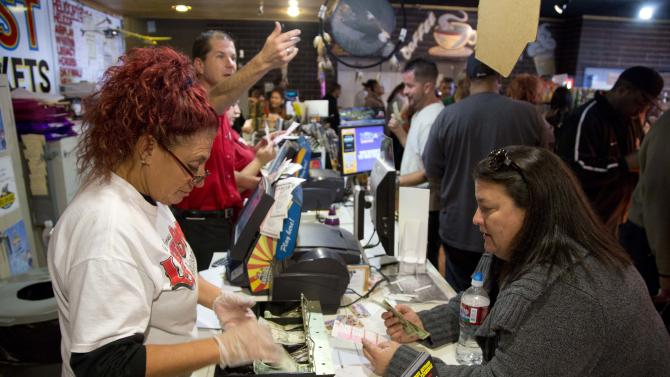 Arizona Last Stop shop employees sell Powerball tickets to customers who waited in line for more than an hour, Tuesday, Nov. 27, 2012, in White Hills, Ariz. There has been no Powerball winner since Oct. 6, and the jackpot already has reached a record level for the game... $500 million.    (AP Photo/Julie Jacobson)