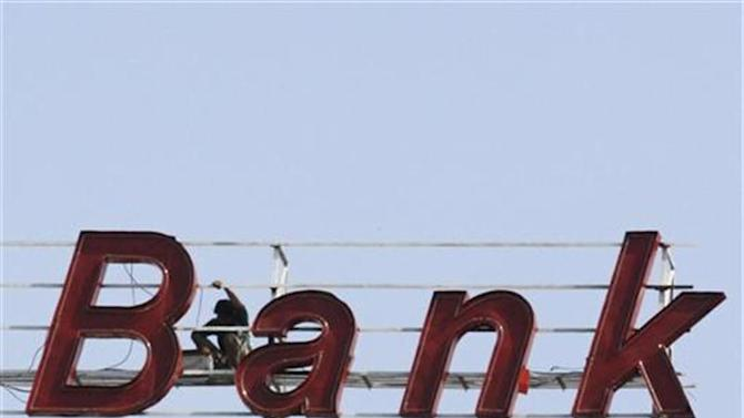 A labourer works on the sign of a bank building in the western Indian city of Ahmedabad