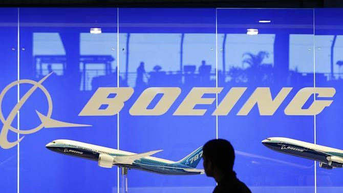A man looks at a scale model of Boeing's 787 dreamliner at their booth at the Singapore Air Show in Singapore