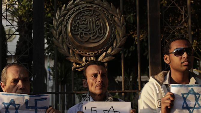 """Egyptians hold papers depicting Israeli flags and swastikas in front of the gate of the Arab League building during a protest in solidarity with Gaza after Israel launched its operation on Wednesday with the assassination of Hamas' top military commander in Cairo, Egypt, Thursday, Nov. 15, 2012. Egypt asked the United States to push Israel to stop its offensive against Hamas militants in the Gaza Strip, warning that the violence could """"escalate out of control,"""" the Foreign Ministry said Thursday. (AP Photo/Nariman El-Mofty)"""