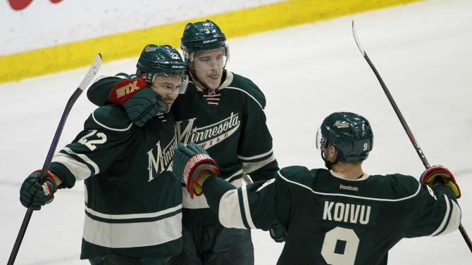 Minnesota Wild right wing Nino Niederreiter , left, of Switzlerand, celebrates with Charlie Coyle, center, and Mikko Koivu (9), of Finland, after Niederreiter's empty-net goal against the St. Louis Blues during the third period of Game 6 of an NHL hockey first-round playoff series in St. Paul, Minn., Sunday, April 26, 2015. The Wild won 4-1 to win the series and advance to the second round. (AP Photo/Ann Heisenfelt)