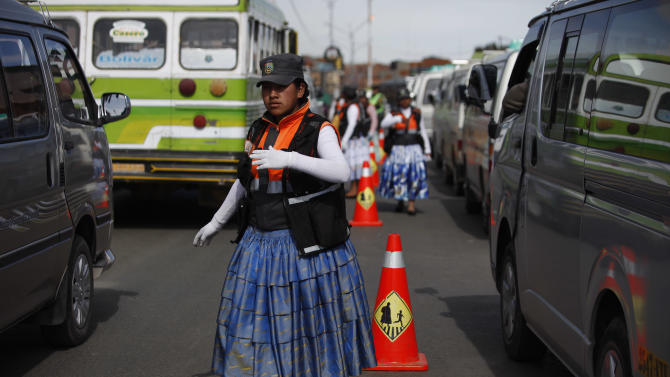 In this Dec. 3, 2013 photo, an Aymara woman cops directs traffic on the streets of El Alto, Bolivia. The women wear the bright petticoats and shawls of indigenous women in the Andes, called cholitas in Bolivian slang, the main difference being that instead of bowler hats they wear khaki green police-style caps. Some don fluorescent traffic vests. (AP Photo/Juan Karita)