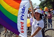 A woman is seen posing with a rainbow flag displaying the words 'Viet Pride' as she prepares to take part in Vietnam's first ever gay pride parade in Hanoi, on August 5. The event, organised by the city's small but growing Lesbian Gay Bisexual and Transgender (LGBT) community, went ahead peacefully with no attempt by police to stop the colourful convoy of about 100 activists