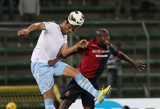 Lazio's Dias, left, and Cagliari's Victor Ibarbo, jumps for the ball during their Serie A soccer match between Cagliari and Lazio, at the Nereo Rocco Stadium in Trieste, Italy, Sunday, May 19, 2013