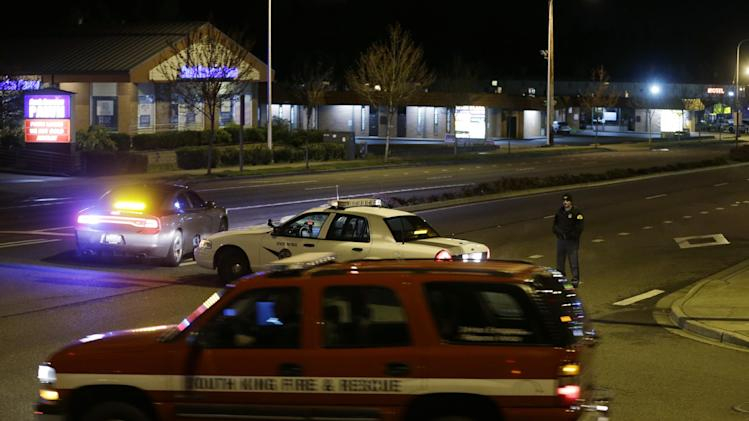 Police and fire vehicles are seen several blocks from the scene of an overnight shooting that police said left five people dead, Monday, April 22, 2013, at an apartment complex in Federal Way, Wash. (AP Photo/Ted S. Warren)