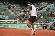 Spain's David Ferrer hits a return to Spain's Marcel Granollers during their Men's Singles 4th Round tennis match of the French Open tennis tournament at the Roland Garros stadium in Paris. Ferrer cruised past countryman Granollers 6-3, 6-2, 6-0