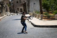 A Syrian rebel fires his rifle as he runs across a road while dodging sniper fire by government forces in Aleppo on August 14, 2012. The old city of Aleppo has become a maze of passageways, some of which are dangerous to cross, whilst others see free movement of civilians