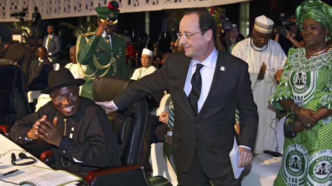 French President Francois Hollande, center, walks past Nigerian President Goodluck Jonathan to deliver a speech during the International Conference on Peace and Security in Abuja, Nigeria, as part of its Centenary celebrations, Thursday, Feb. 27, 2014. Hollande is in Nigeria for a one-day official visit. (AP Photo/Philippe Wojazer, Pool)