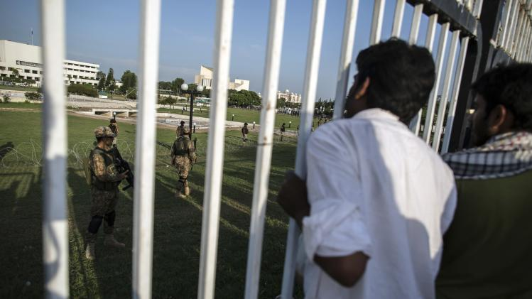 """Supporters of Tahir ul-Qadri, Sufi cleric and leader of political party Pakistan Awami Tehreek (PAT), stand behind a fence in front of the Parliament house building, as soldiers secure the area, during the """"Revolution March"""" in Islamabad"""