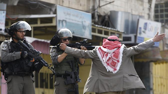 Palestinian man prevents an Israeli border policeman from shooting at protesters during clashes in the West Bank city of Hebron